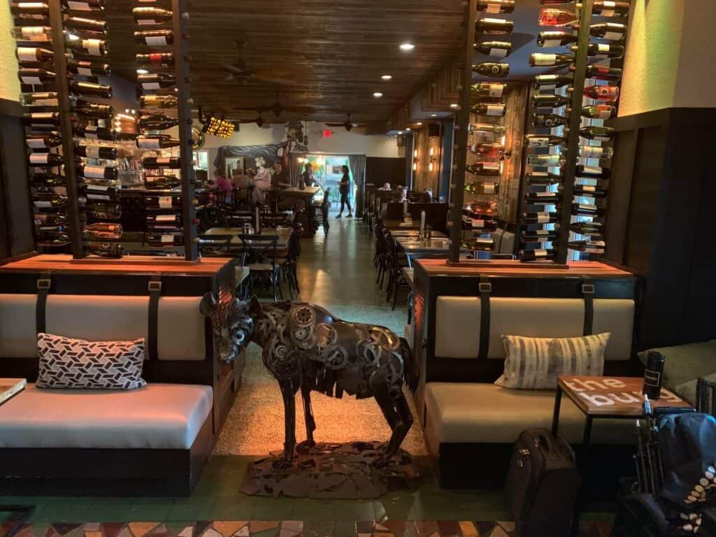 steel hyena sculpture inside a lobby with wine racks behind it.