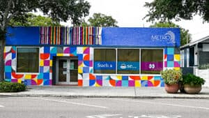 exterior of a single floor retail building with a rainbow colored mural
