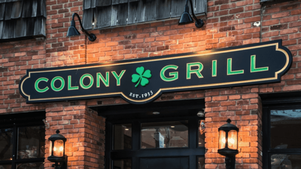 brick exterior with a black and green sign that reads Colony Grill