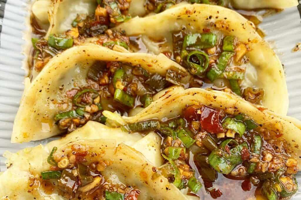 dumplings covered in sauce and green vegetables