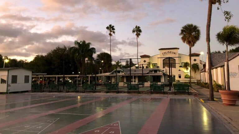 exterior of a shuffleboard club with rain on the courts and palm trees in the background
